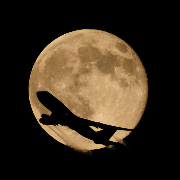 夏の夜の満月とジェット機